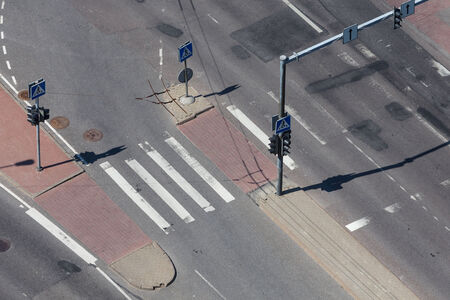 high angle view of an empty street intersection with cross walk markings, traffic signal lights photo