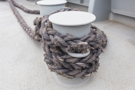 cleat: Close-up of a mooring rope with a knotted end tied around a cleat on a wooden pier Nautical mooring rope Stock Photo