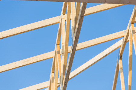 residential home: New residential construction roof home framing against a blue sky
