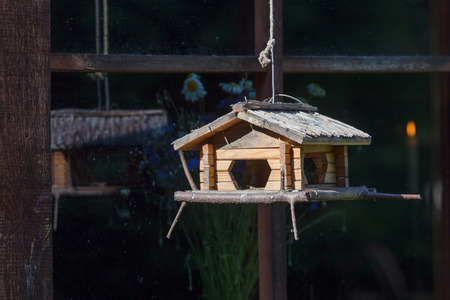 Handcrafted log cabin birdhouse feeder. Close up photo