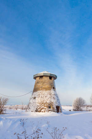 truncated: Estonian truncated windmill, a house and snow Stock Photo