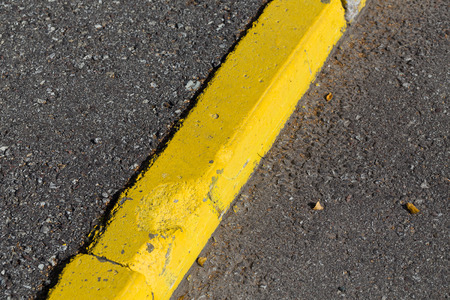 Yellow curb stone border and asphalt road photo