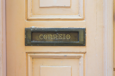 Letters slot at Old Wooden Door in Lisbon, Portugal. Correio letters are on the front