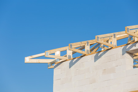roof framing: New residential construction roof home framing against a blue sky
