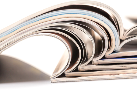 Stack of magazines on white background with reflection photo