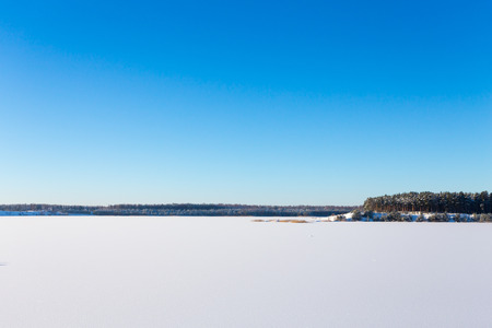 Frozen lake with ice and snow, sunny winter day. Forest photo