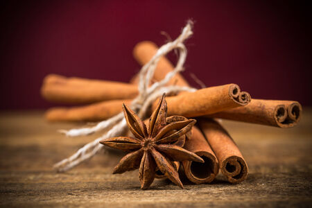 Close up of cinnamon sticks and star anise on rustic wood background photo