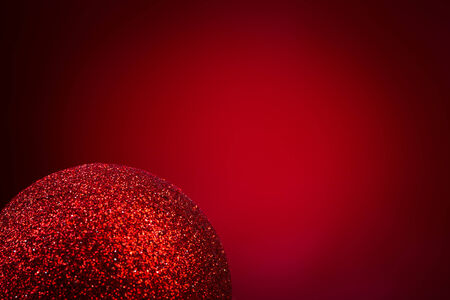 red christmas ball on red background, close up photo