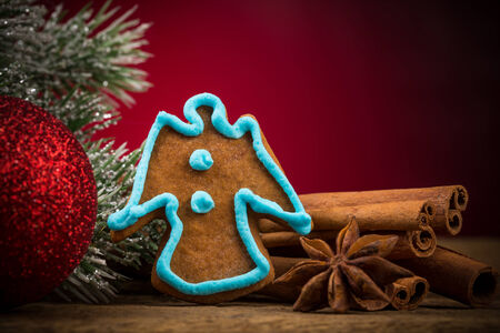 Christmas gingerbread cookie, red ball and anise on wooden table with red background photo