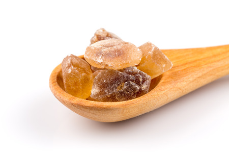 hyperglycemia: brown caramelized sugar in a wooden spoon on a white background