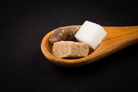 refined: White refined and brown sugar in wooden spoon on dark stone background Stock Photo