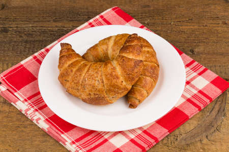 buttery: Fresh baked croissants on a plate on wooden background