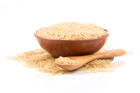 brown rice over the spoon on a white background Standard-Bild