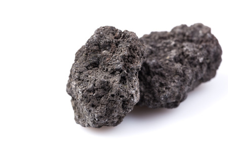 Black lava rock from volcano on a white background Imagens