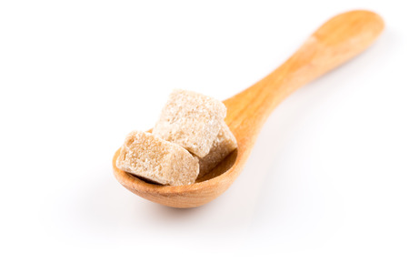 hyperglycemia: brown sugar in a wooden spoon on a white background
