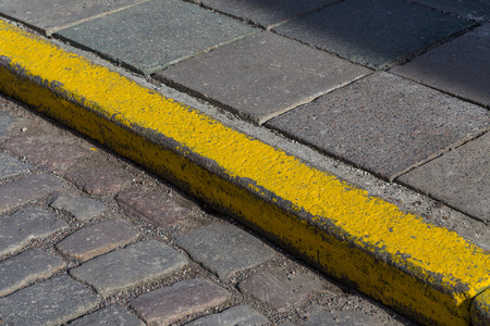 curb: Yellow curb stone border in an old town road