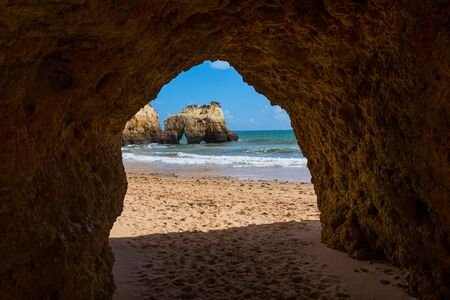 claustrophobia: Hole of a big cave in the stones of the beach, Algarve Portugal