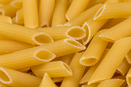 Closeup photo of uncooked italian penne pasta background photo