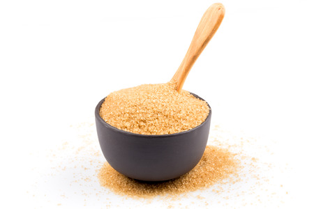 brown sugar in a bowl with wooden spoon  isolated on white photo