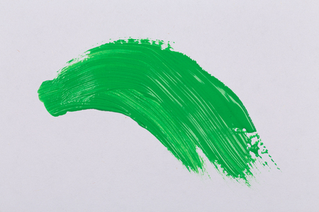 green stroke of the paint brush on white paper photo