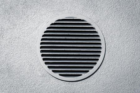 Circle vent window on metallic concrete wall photo