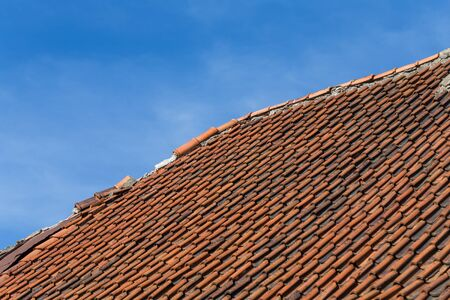 broken terracotta tile on a roof of old house photo