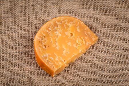 full of holes: Italian Cheese on hessian background close up Stock Photo