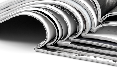 Stack of magazines on white background with reflection