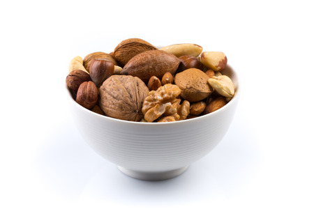Large diversity of healthy nuts in a white bowl - isolated Banco de Imagens