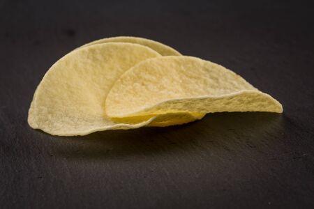 channeled: Potato chips on a black  stone board background