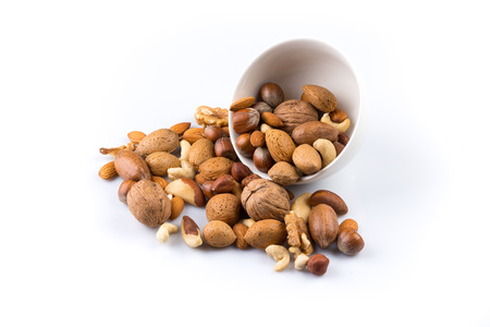 Large diversity of healthy nuts in a white bowl - isolated Standard-Bild