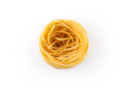 Fettuccine pasta nest isolated on white background