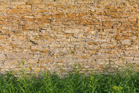foreground: stone wall with grass foreground at sunset Stock Photo
