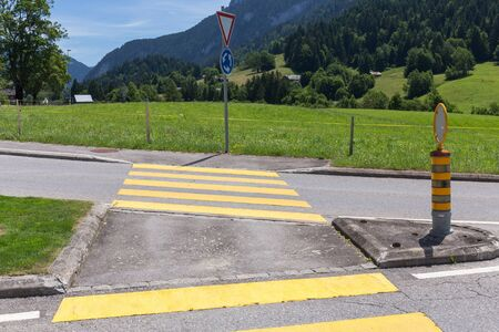 rural road: yellow road crossing in rural alps countryside Stock Photo