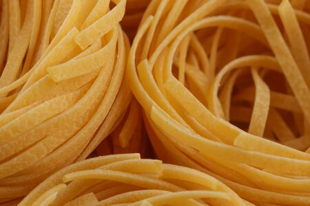 fettuccine: dried italian pasta, fettuccine nests, abstract food background, closeup shot Stock Photo