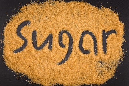 fine cane: word sugar written in brown granulated sugar on dark stone background