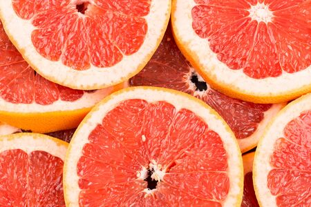 red background: Abstract red background with citrus-fruit of grapefruit slices. Close-up Stock Photo