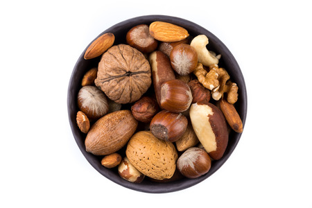 mixed nuts: Large diversity of healthy nuts in a dark stone bowl - isolated