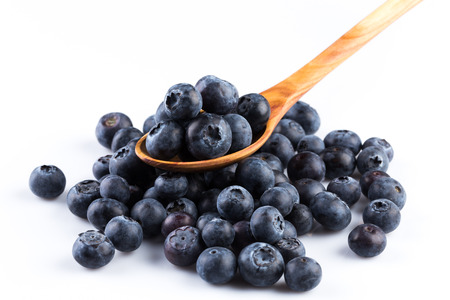 Fresh blueberries in wooden spoon on white background
