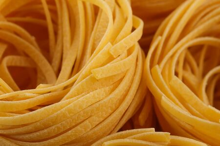 abstract food: dried italian pasta, fettuccine nests, abstract food background, closeup shot Stock Photo