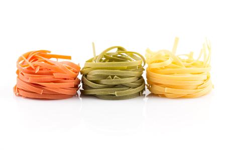 pastas: tres colores nido rollo de pasta sobre un fondo blanco Foto de archivo
