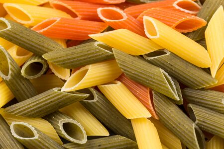 horizontal format: Color penne pasta. Tomato, spinach and wheat pastas in horizontal format Stock Photo