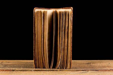 old desk: ancient book shot on black background