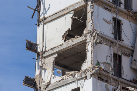 deconstruct: Pieces of Metal and Stone are Crumbling from Demolished building