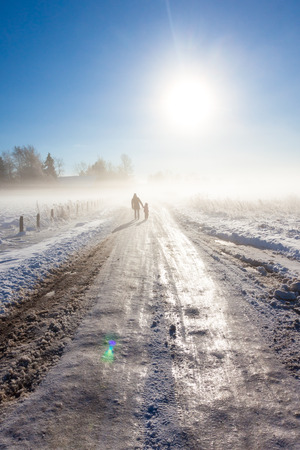snow road: Mother and child on foggy snow road near farm