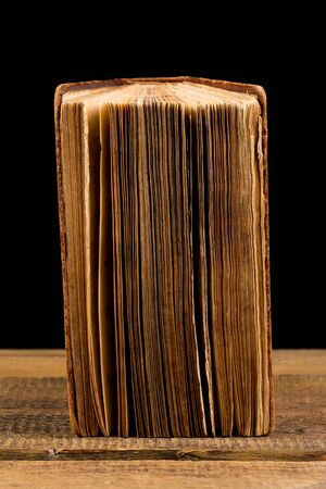 bad condition: ancient book shot on black background. The book is in bad condition. Stock Photo