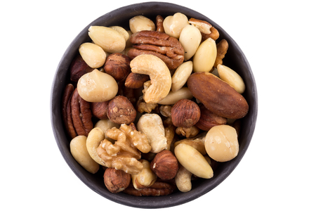 mixed nuts: Large diversity of healthy nuts in a dark bowl - isolated