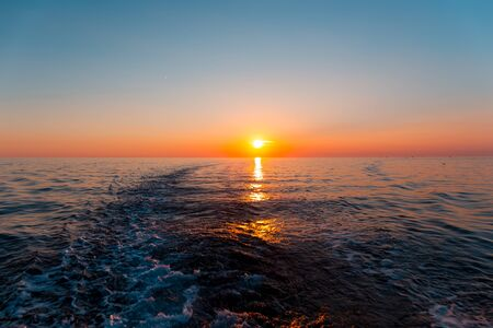 trace: Sunset in the sea and a trace from the ship