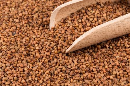 Uncooked buckwheat on wooden spoon. premium buckwheat groats on white background