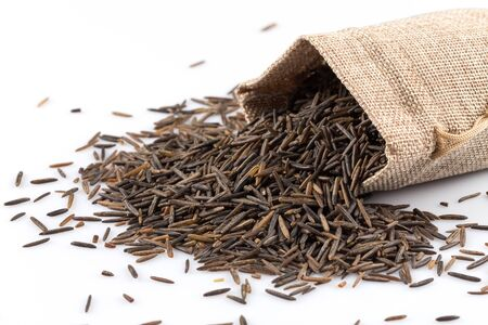 processed grains: Close up image of a heap of wild rice on white background in a hessian sack